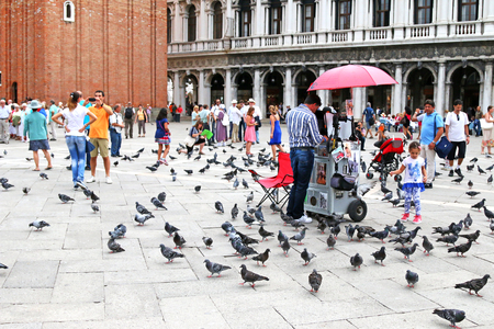 the campanile: People walking around at St Marks Campanile Campanile di San Marco among a lot of pigeons and shops in Venice, Italy on September 15, 2014. St Marks Campanile is located in the Piazza San Marco. Editorial