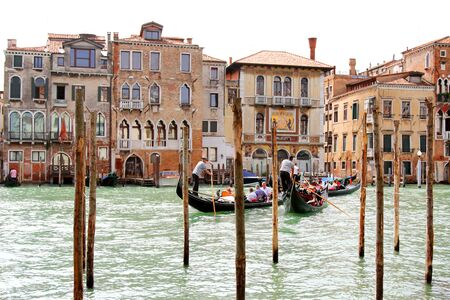 Gondoliers carrying tourists on Grand Canal crossing to the Palazzo Salviati in Venice, Italy on September 15, 2014. Gondola boats is still the main means of transportation in Venice. Editorial