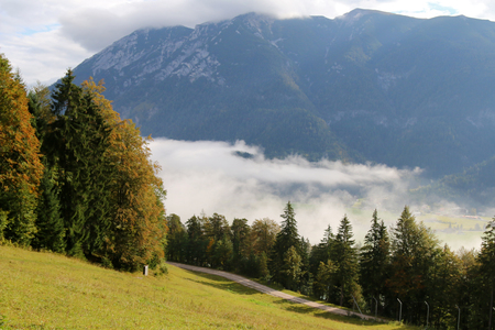 early fog: Landscape view of forest, mountain and a village blanketed with early morning fog during Autumn in Tyrol, Austria Stock Photo