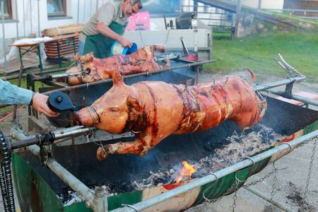 seasoned: A man using air blower Fire starter for charcoal for spit roasting in Tyrol, Austria on September 17, 2014. Roasting piglet on a spit is one of food during Oktoberfest celebration. Editorial