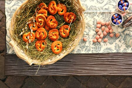 easter nest: A basket full of Pretzel on dried hay and some Easter chocolate balls on the table Stock Photo