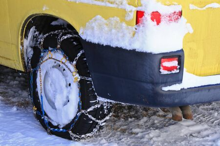 safety device: A yellow car with snow chains tire chains attached to the drive wheels parking on snowy path during winter