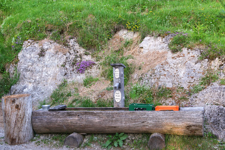 provided: Old wooden trough with cases of beer immersing in cold water. Alcoholic beverages are provided to hikers to serve themselves after inserting money in a box. The word Kein Trink Wasser is German phrase for no drinking water.