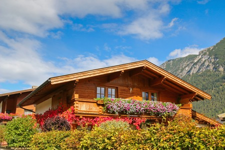 austrian village: Traditional wooden house decorated with colourful flowers on the balcony in Tyrol, Austria