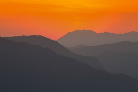 ranges: View of the sky turning orange, red during sunset behind mountain ranges in Europe