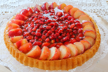 The classic Biskuit or German Biscuit, known as Sponge Cake decorated with fresh wild strawberries, garden strawberries, and peach.