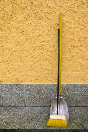 old styled: An old styled yellow broom and metal dustpan leaning on yellow wall Stock Photo
