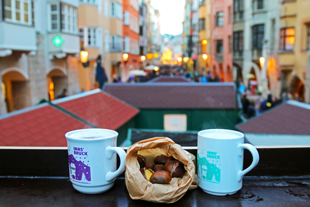 december 21: Cups of typical hot mulled gluhwein wine, Punsch and roasted chestnuts at Christmas Market in Innsbruck, Austria on December 21, 2014.