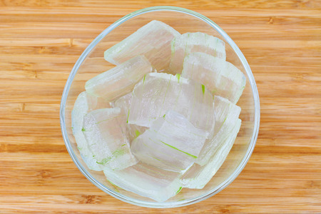 sunburn: A glass bowl full of freshly picked Aloe vera plant, peeled and cut into pieces on wooden background. Fresh Aloe Vera is natural remedy for sunburn relief and cure many things.