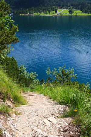 hiking path: Hiking path along the Achen Lake Achensee with high mountain background during summer time Stock Photo
