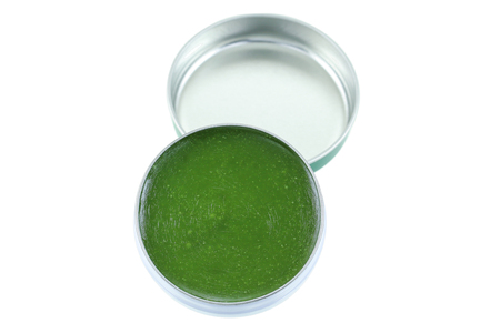 balm: A small balm jar full of medicated ointment in green color, isolated on white