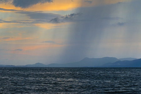 severe weather: Evening view of the sky with bad weather with severe rainstorm from afar over the sea Stock Photo
