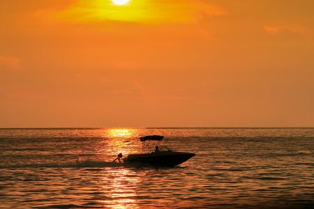 Avond uitzicht van de gouden zonsondergang foto met een silhouet van een snelle boot drijvend op de zon reflectie
