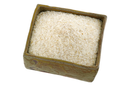 psyllium: A squared clay bowl full of dried psyllium husk fiber to relieve constipation, irritable bowel syndrome, isolated on white