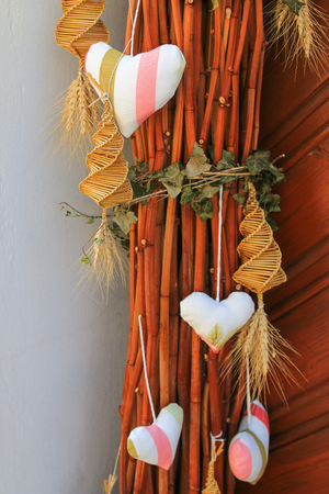 dolly: Hearts and spirally woven corn dolly hanging on dried branch as a holiday decoration