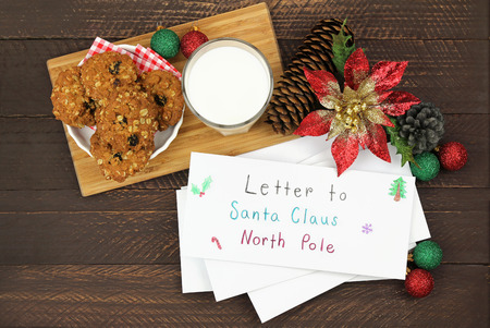 envelops: Homemade cookie next to a glass of milk and white envelops with letter to Santa Claus inside on a wooden background