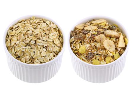 avena en hojuelas: tazas blancas llenas de copos de avena cruda lado de muesli Empaquetado con diversos frutos secos y semillas. Foto de archivo