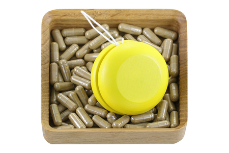 regain: A wooden box full of herbal medicines with yellow YoYo, isolated on white represent the idea of Yo-Yo dieting Effect Stock Photo