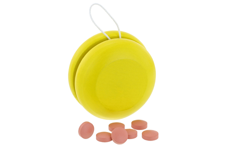 regain: Yellow YoYo next to pink medicines , isolated on white represent the idea of Yo-Yo dieting Effect