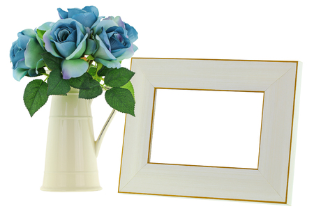 arrangements: A yellow vintage enamel ceramic jug vase with blue green roses next to blank beige wooden picture frame with golden border, isolated on white background Stock Photo