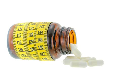 A brown medicine bottle with yellow measuring tape wrapped around and white capsules falling out, isolated on white background Stock Photo