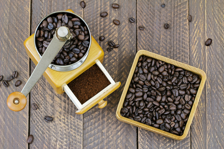 powdery: Vintage wooden coffee hand grinder with ground coffee inside next to a wooden box full of very dark roasted Robusta coffee beans