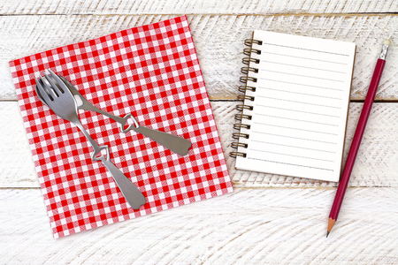 Top view of red gingham paper napkin with cute fork, spoon on it next to a blank white notebook and a pencil, on a white wooden floor