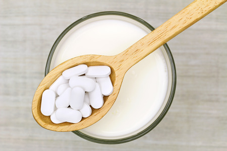 Top view of a wooden spoon of white Calcium carbonate tablets above a glass of fresh milk on a gray background Stockfoto