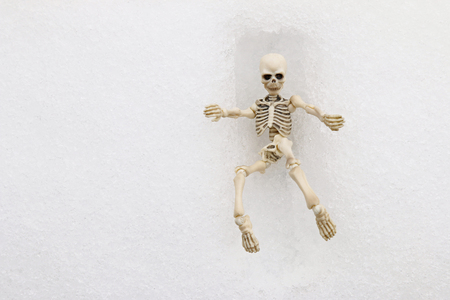 cremated: White skeleton trying to get out of a square grave made of snow during winter time Stock Photo