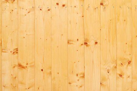 Hintergrund der hellen hölzernen Wand in der gelben Farbe mit einem natürlichen Kiefernholzmuster und -nägeln