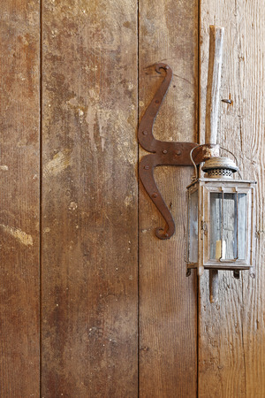 barn door: A wooden door made of barn wood with rustic vintage candle lamps hanging on the handle