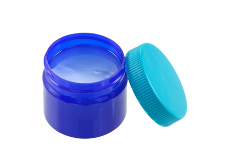 cold remedy: A small blue green jar full of  mentholated topical ointment isolated on white