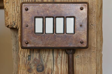 bakelite: Closeup of vintage bakelite toggle light switch in brown on wooden pole