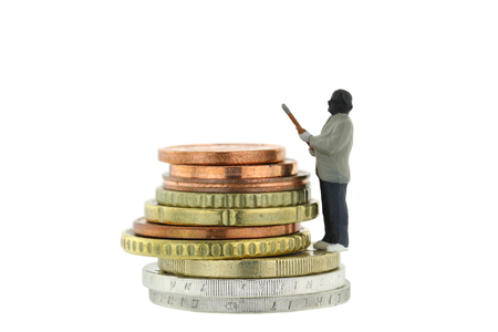 euro coins: Closeup of Miniature robber model standing on a pile of Euro coins, concept for money robbery