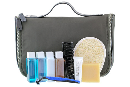 Black traveling cosmetic bag with toiletries in the front, isolated on white