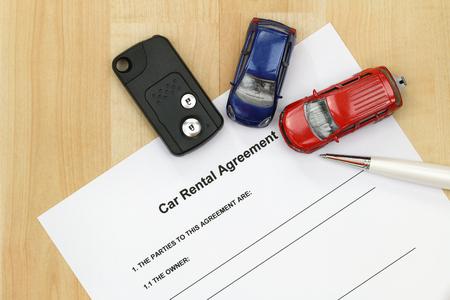 Closeup of car rental agreement paper next to a remote car key, a pen and mini car models