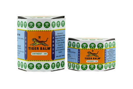 relieving pain: BANGKOK, THAILAND - DECEMBER 2015 : Big and small packages of Tiger Balm isolated on white  in Bangkok, Thailand on December 21, 2015. Tiger Balm is medicinal ointment made from herbs that has pain-relieving remedy