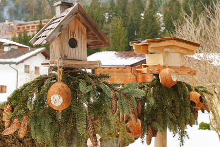 feeders: Two wooden bird feeders decorated with pine tree branches with coconut shell suet treats hanging