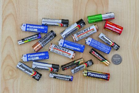BANGKOK, THAILAND - OCTOBER 2015 : Primary cell and rechargeable battery from different brands on a wooden background in Bangkok, Thailand on October 22, 2015. 新聞圖片