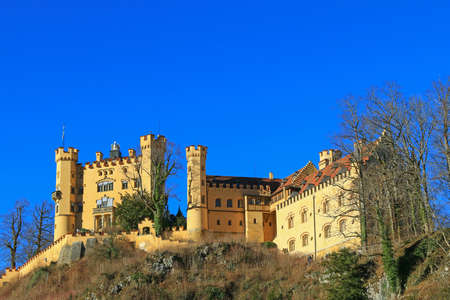 schwangau: SCHWANGAU, GERMANY - DECEMBER 2015 : The facade of Hohenschwangau Castle situated on the hill in Schwangau, Germany on December 26, 2015. It is the neo-gothic styled where King Ludwig II. spent his childhood. Editorial
