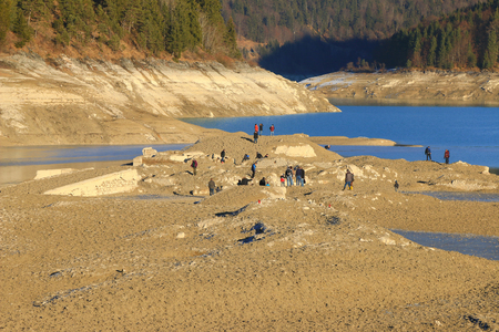 emptied: UPPER BAVARIA, GERMANY - DECEMBER, 2015 : People exploring the ruin of sunken old village Fall at Sylvenstein Reservoir dam in Upper Bavaria, Germany on December 30, 2015. Editorial