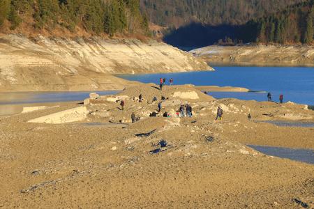 sunken: UPPER BAVARIA, GERMANY - DECEMBER, 2015 : People exploring the ruin of sunken old village Fall at Sylvenstein Reservoir dam in Upper Bavaria, Germany on December 30, 2015. Editorial