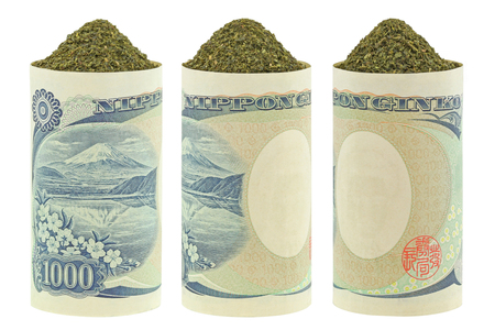 green and white: Closeup of dried Japanese green tea inside rolls of Japanese Yen banknotes, isolated on white Stock Photo