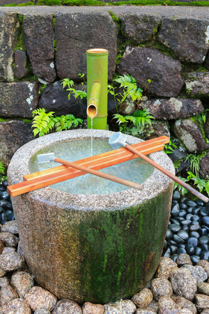 stone wash: Water running out through bamboo pipe to stone water basin. It is to purify oneself before visiting shrine in Japan