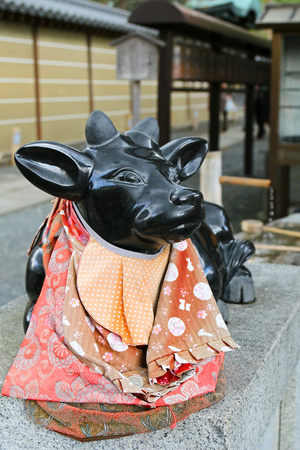 believed: Soft forcus of sacred statue of black marble cow outside Kadai-ji Temple in Kyoto, Japan. Its believed that a gently stroke any part of the statue then the corresponding part of your body, pain will go away.