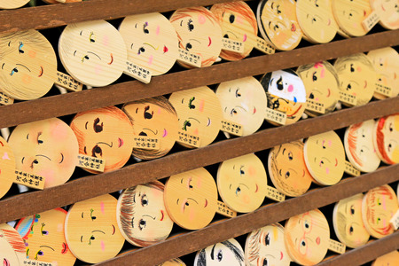 face paint: Shallow depth of field of mirror-shaped wooden preyer tablet Kagami ema in Kyoto, Japan. Its believed to paint the face, make a wish and your face will become more beautiful