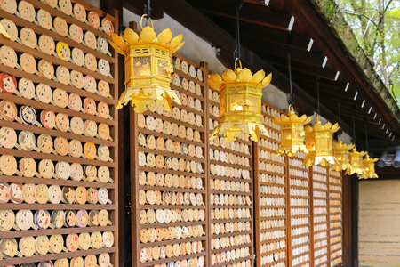 ema: Shallow depth of field of beautiful golden lanterns hanging  in front of mirror-shaped wooden preyer tablets called Kagami ema at Kawai-jinja Shrine, in Kyoto, Japan
