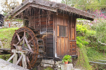 waterwheel: Traditional wooden water wheel spinning at Tsumago - juku in Tsumago, a preserved historical town in Japan.