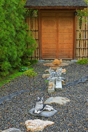 lucky charm: Soft focus of Japanese ceramic cats as lucky charm to decorate the zen styled garden in Japan. Focusing on the front one.