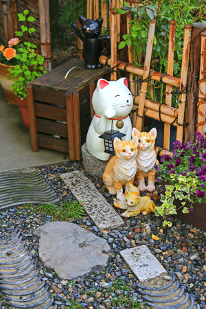 maneki: A group of Japanese ceramic cats called maneki-neko as lucky charm to decorate the zen styled garden in Japan.